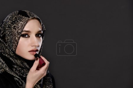 Portrait of Muslim woman painting her lips with a lipstick