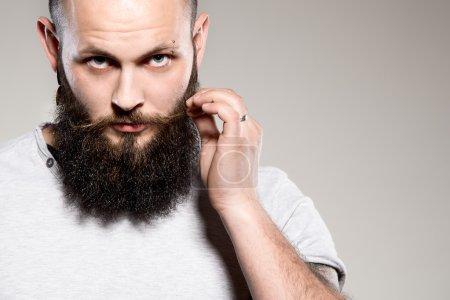 Photo pour Homme barbu toucher moustache - fond gris - image libre de droit