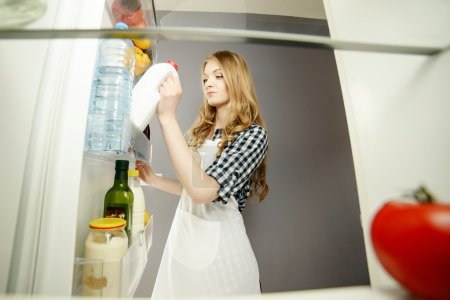 A woman pulls out a bottle of milk from the refrigerator