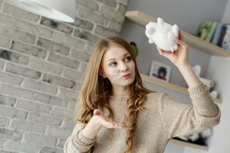 Photo pour Woman trying to find more money in the piggy bank, lifting it over his head. - image libre de droit