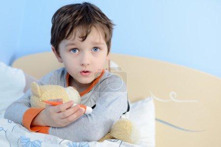 The little boy is sick. He lies in bed.