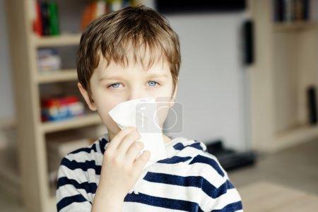 Little boy blows his nose