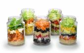 Salad in glass jar on white background, no lid