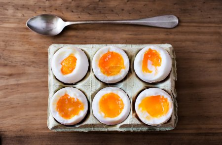 Photo for Half a dozen soft boiled eggs in a crate cardboard box. - Royalty Free Image