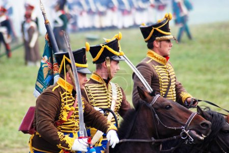 Reenactors dressed as Napoleonic war soldiers ride horses