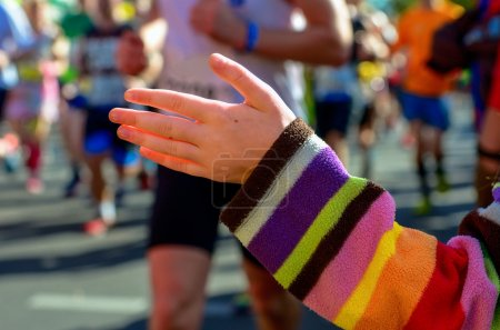 Blurred background: marathon running race, support runners on road, child's hand giving highfive, sport concept
