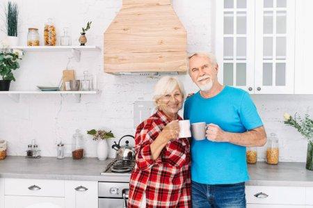 Photo pour Conjoints âgés dans la cuisine confortable avec des tasses dans les mains. couple aîné aux cheveux gris regarde la caméra avec des sourires aimables - image libre de droit