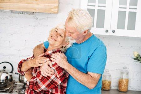 Photo pour Les conjoints âgés s'embrassent dans la cuisine. Couple aux cheveux gris en chemises à carreaux décontractées passer du temps ensemble à la maison - image libre de droit
