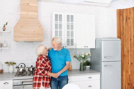 Photo pour Les conjoints âgés se tenant la main et se regardent dans la cuisine confortable - image libre de droit