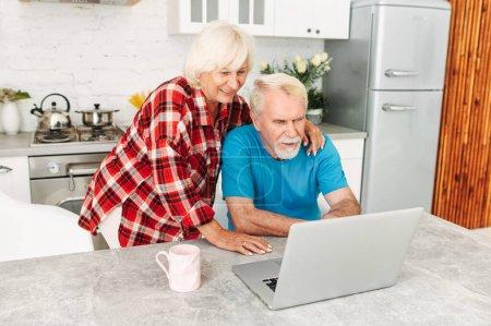 Photo pour Les conjoints âgés dans l'étreinte en utilisant un ordinateur portable dans la cuisine à la maison - image libre de droit