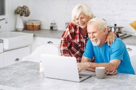 Photo pour Joyeux conjoints âgés passent du temps ensemble en utilisant un ordinateur portable. Couple de personnes âgées font du shopping en ligne, regarder des nouvelles ou websurfing - image libre de droit