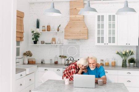 Photo pour Les conjoints âgés utilisant un ordinateur portable à la maison. Une femme et un mari passent du temps libre en ligne dans un filet métallique - image libre de droit