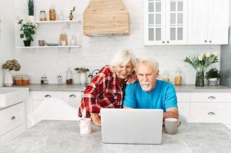 Photo pour Les conjoints âgés passent du temps ensemble en utilisant un ordinateur portable. Couple de personnes âgées font du shopping en ligne, regarder des nouvelles ou websurfing - image libre de droit