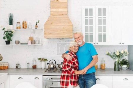 Photo pour Épouses âgées dans la cuisine confortable tenant la main. couple aîné aux cheveux gris regarde la caméra avec des sourires aimables - image libre de droit