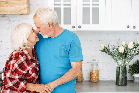 Photo pour Un portrait des conjoints âgés dans la cuisine. Femme aux cheveux gris et mari tenant tendrement la main et se regardant dans les yeux. Concept d'amour et de soins - image libre de droit