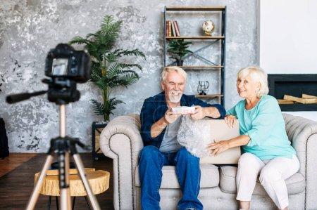 Photo pour Couple senior moderne enregistre déballage sur vidéo pour le blog. Les conjoints âgés sont assis sur le canapé avec une boîte de colis, caméra sur trépied en face d'eux - image libre de droit