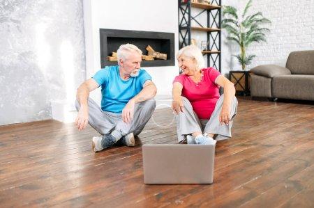 Photo pour Couple de personnes âgées allant pratiquer le yoga à la maison avec un cours vidéo en ligne. Les conjoints âgés en vêtements de sport se regardent assis sur le sol à la maison devant l'ordinateur portable - image libre de droit