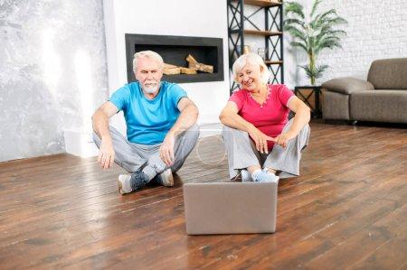 Photo pour Couple de personnes âgées allant pratiquer le yoga à la maison avec un cours vidéo en ligne. Les conjoints âgés en tenue de sport regardent sur l'écran de l'ordinateur portable assis sur le sol à la maison - image libre de droit
