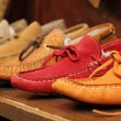 Colorful moccasins style shoes on shelf by italian...