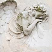 closeup of antique angelic relief on tombstone