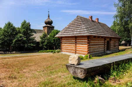 Wooden house next to the antique regional church in historic Polish village, Lesser Poland, Poland