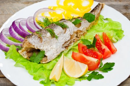 Fish hake baked with vegetables on a plate...