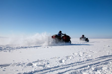 man riding quad bike on snowy winter field