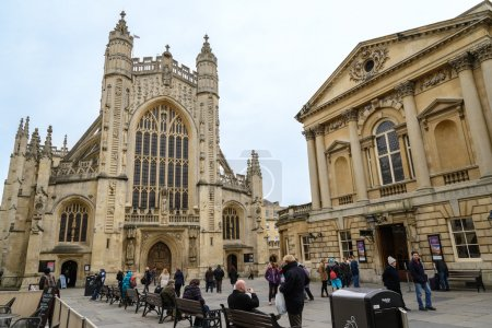 BATH, UK - MARCH 19: Tourists and locals enjoy a sunny day in the courtyard of the historic Bath Abbey and Roman Baths on March 19, 2013 in Bath, UK. Bath receives 4.5M visitors a year.