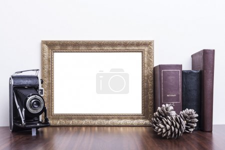 Photo for Golden Frame with old books and old camera on wood table - Royalty Free Image