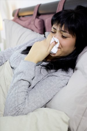 Sick woman sneezing nose in bed unhappy ill