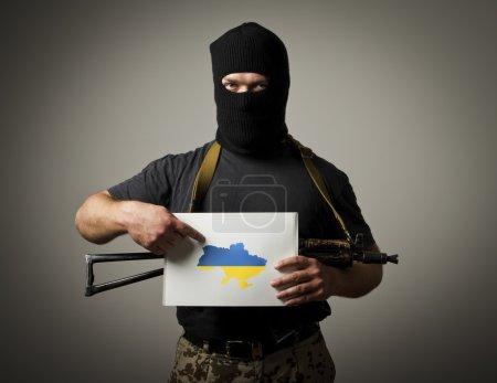 Photo pour Un homme masqué avec une arme tient un livre blanc avec une carte de l'Ukraine . - image libre de droit