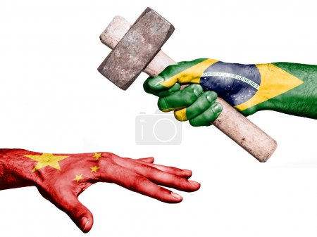 Photo pour Flag of Brazil overprinted on a hand holding a heavy hammer hitting a hand representing the China. Conceptual image for political, fiscal or social aggressions, penalties, taxation - image libre de droit