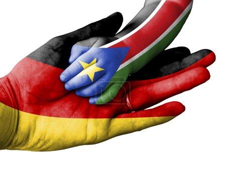 Photo pour Pavillon de l'Allemagne superposées de la main d'un homme adulte, tenant d'une main de bébé avec le drapeau du Sud-Soudan surimprimés. Image conceptuelle pour l'aide, aide, assistance, secours. Isolé sur fond blanc - image libre de droit