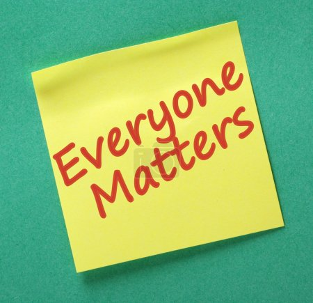 Photo pour The phrase Everyone Matters written in red ink on a yellow sticky note on a green paper background - image libre de droit