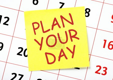 Photo for Advice to Plan Your Day in red text on a yellow sticky note posted on the page of a calendar as a reminder - Royalty Free Image