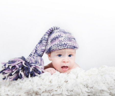 Newborn baby in colorful funny long hat looking at the camera