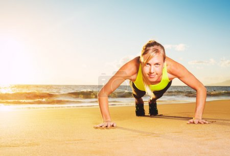 Photo for Fitness young woman doing push ups on beach at sunset. Outdoor workout. - Royalty Free Image