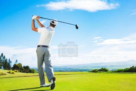 Photo pour Man Playing Golf on Beautiful Sunny Green Golf Course. Hitting Golf Ball down the Fairway from the Tee with Driver. - image libre de droit