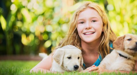 Photo for Adorable Cute Young Girl Playing and Hugging Puppies - Royalty Free Image