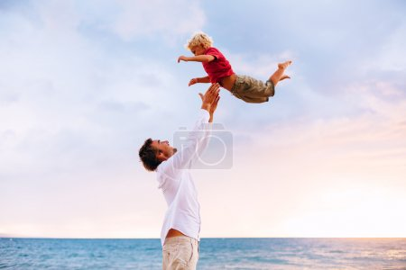 Photo for Father and Son Playing on the Beach by the Ocean - Royalty Free Image