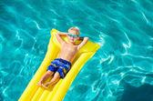 Chlapec, relaxace a zábava v bazénu na žlutý vor