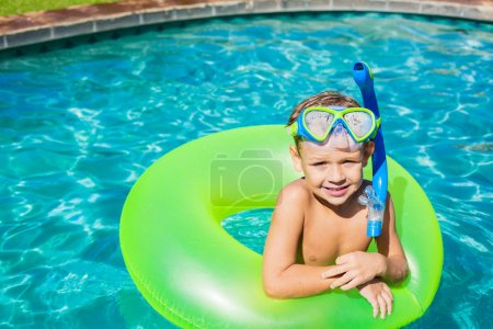 Photo for Young Kid Having Fun in the Swimming Pool On Inner Tube Raft. Summer Vacation Fun. - Royalty Free Image
