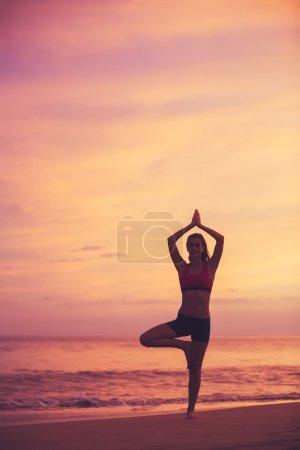 Photo pour Silhouette de jeune femme pratiquant le yoga sur la plage au coucher du soleil. Mode de vie sain et actif . - image libre de droit