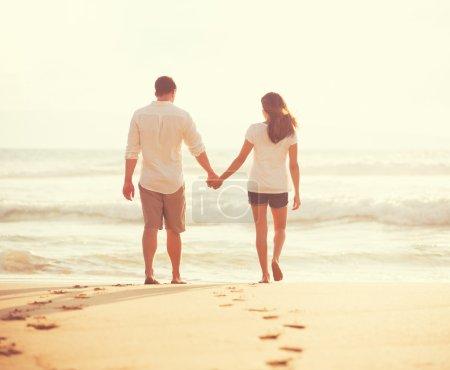 Photo pour Jeunes amoureux romantiques marchant sur la plage au coucher du soleil en vacances - image libre de droit
