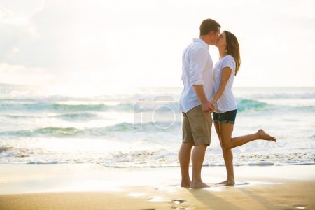 Young Couple Kissing on the Beach at Sunset