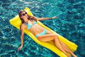 Krásná žena, relaxační, plovoucí na voru v bazénu
