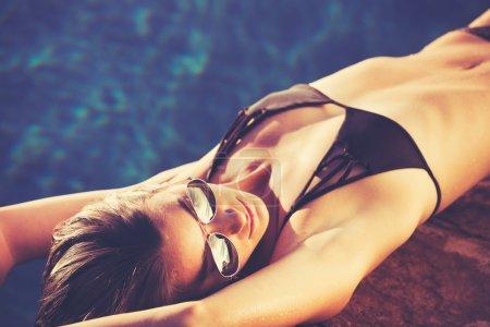 Beautiful Woman in Bikini Relaxing By the Pool at Sunset