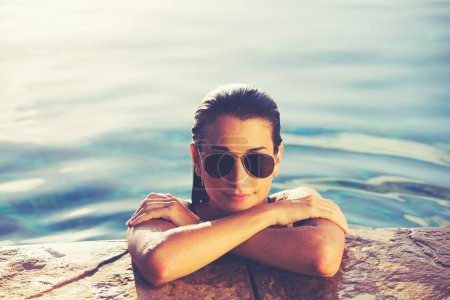 Photo for Beautiful young woman relaxing in pool at sunset, Luxury resort fashion lifestyle - Royalty Free Image