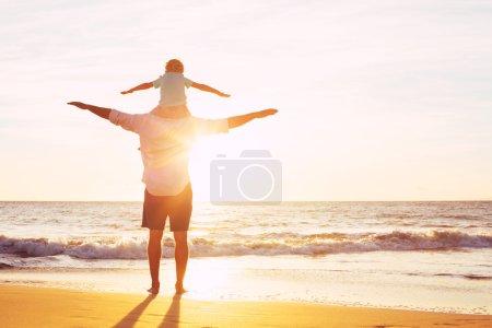Photo pour Père et fils jouant sur la plage au coucher du soleil, avoir qualité famille temps ensemble. - image libre de droit