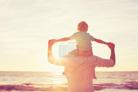 Photo pour Père et Fils jouant sur la plage au coucher du soleil, passer du bon temps en famille . - image libre de droit